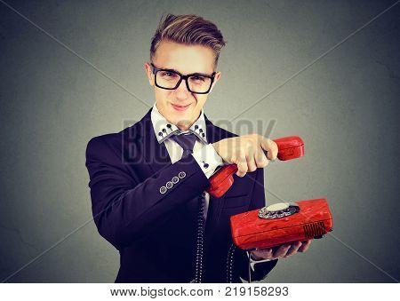 Annoyed sly business man hanging up telephone