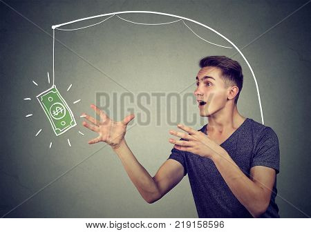 Incentive trap business concept. Young man running towards a dollar symbol trying to catch it.