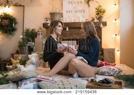 couple of beautiful young women in a room decorated for celebrating the new year and christmas
