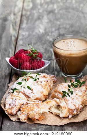 homemade fresh almond croissant with cup of cappuccino on rustic wooden table