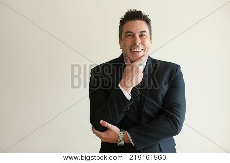 Portrait of interested mid adult Caucasian businessman wearing suit touching chin, looking at camera and smiling. Interest and curiosity concept