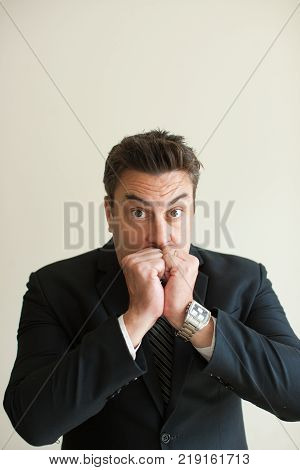 Portrait of stressed mid adult Caucasian businessman biting nails and looking at camera. Worry and depression concept