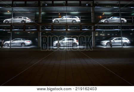 MUNICH, GERMANY - DECEMBER 11, 2017 : A view of the Mercedes Benz dealership building exterior with cars exhibited in the shop windows at night in Munich, Germany.