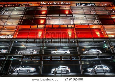 MUNICH GERMANY - DECEMBER 11 2017 : A view of the Mercedes Benz dealership building exterior with cars exhibited in the shop windows at night in Munich Germany.