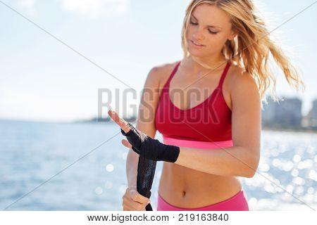 Young blonde woman wrapping bandage on hands at seashore martial arts