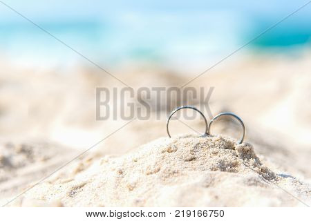 Wedding rings for couple lover on the sandy beach. Engagement rings in honeymoon vacation in tropics. Valentine Concept. soft and select focus