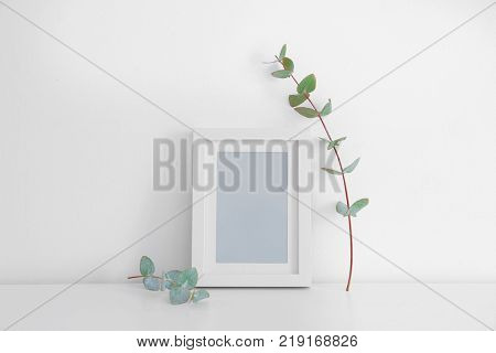 Empty frame and eucalyptus branch on table near white wall