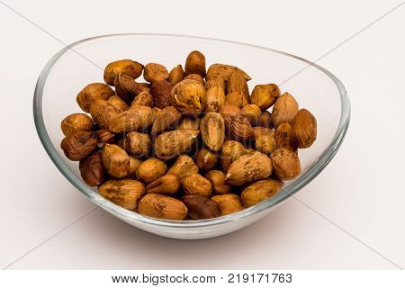 Pile of pealed hazelnuts in the glass bowl