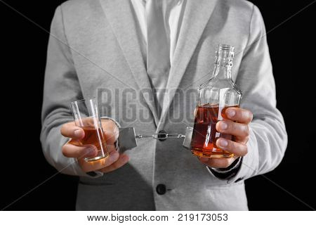 Man in handcuffs with bottle and glass of brandy on dark background. Alcohol dependence concept