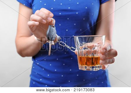 Woman in handcuffs with glass of alcohol and car key against light background. Don't drink and drive concept