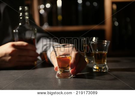 Woman with bottle and glass of brandy in bar. Alcohol dependence concept