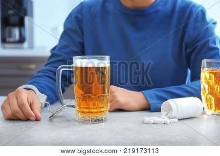Man in handcuffs with mug of beer and drugs indoors. Alcohol dependence concept