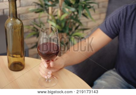 Man with glass of wine sitting at wooden table indoors. Alcohol dependence concept