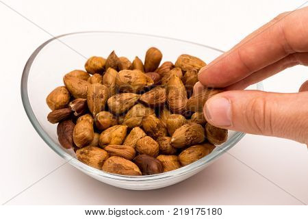 person taking pealed hazelnuts out of the glass bowl