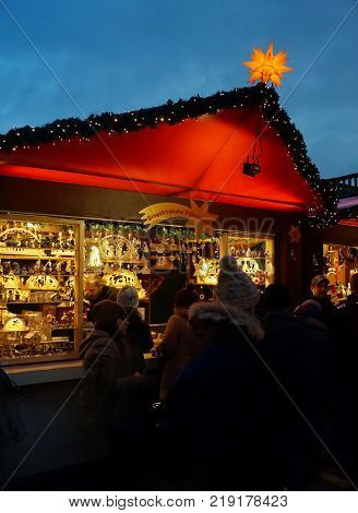 Cologne, Germany - December 16, 2017: German Christmas Market at Night. Shoppers visit vendors selling gifts, wine and gourmet food at the annual Cologne Cathedral Christmas market.