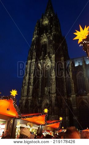 Cologne, Germany - December 16, 2017: German Christmas Market at Night. Shoppers visit vendors selling gifts, wine and gourmet food at the annual Cologne Cathedral Christmas market with the historic cathedral in the background
