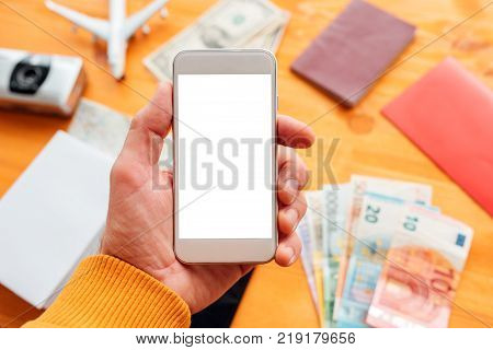 Travel planning and booking app for mobile phone. Man holding smartphone with blank screen as mock up copy space for text or graphics related to holiday vacation journey trip.
