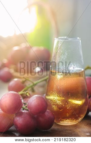 Fresh grape wine in glass over the wooden background.