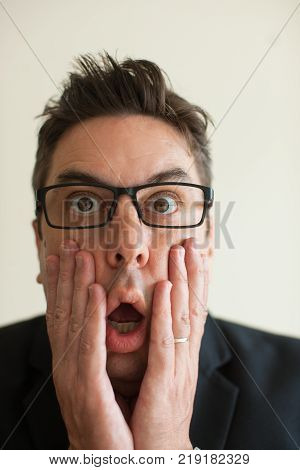 Close-up of surprised or terrified face of mid adult Caucasian businessman wearing eyeglasses holding head in hands. Surprise and fear concept
