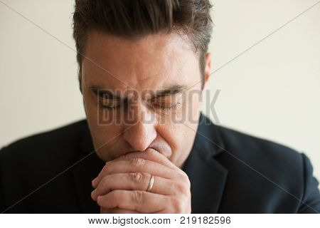 Close-up of sad, pensive or concentrated face of mid adult Caucasian businessman. Praying businessman. Regret and depression concept