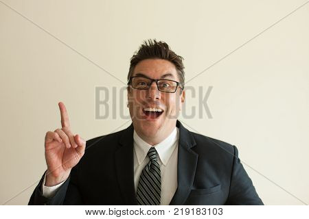 Portrait of happy mid adult Caucasian businessman wearing glasses raising finger and looking at camera. Having idea concept