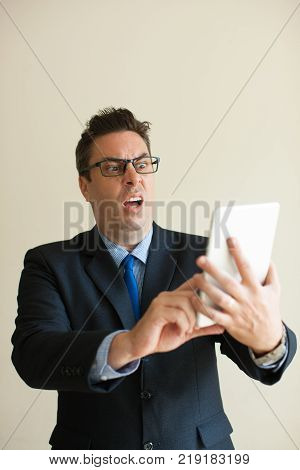 Portrait of mid adult Caucasian businessman wearing glasses using digital tablet and looking at it with indignation. Failure in communication concept