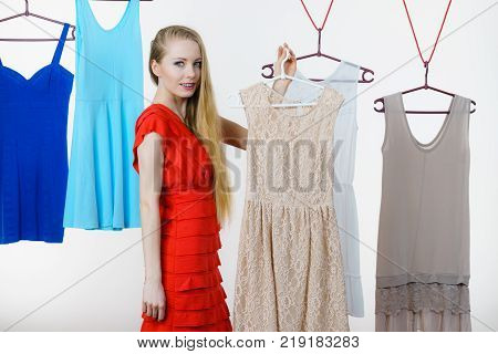 Young blonde long hair woman in clothes in shop or wardrobe choosing summer outfit dresses hanging on clothing hangers on white. Sale shopping fashion and style concept
