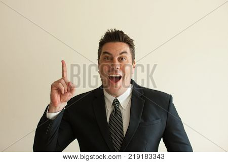 Portrait of excited mid adult Caucasian businessman raising finger and looking at camera. Having idea concept