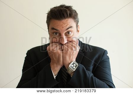 Portrait of frightened mid adult Caucasian businessman biting nails and looking at camera. Fear and guilt concept