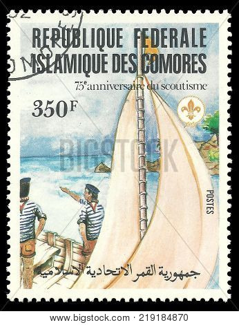 Comoros - CIRCA 1982: stamp printed by Comoros  Multicolor memorable Edition offset printing on Topic of 75 Years of Scouting, Shows Scouts Sailboat and people nearby
