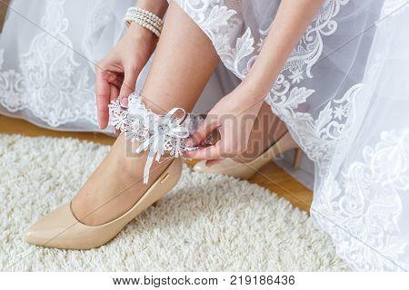 Garter On The Leg Of A Bride, Slim Sexy Bride In Wedding Luxury Dress Showing Her Silk Garter. Woman