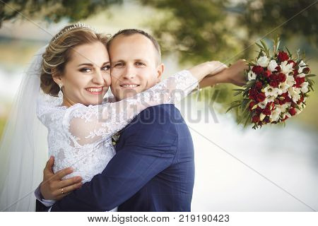 The bride and groom in nature. Bride is hugging the groom. Wedding day. The best day of a young couple