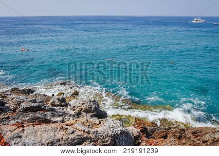 rocky shore of blue sea. Waves on stones at tropical sea. Waves are beating against rocky shore of sea on sunny summer day
