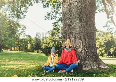 Yoga and meditation concept. Beautiful young woman in knitted clothes and small child keep eyes closed meditate outdoors in green park feel relaxed calm and peaceful keep hands in mudra sign