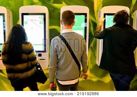 MILAN, ITALY - CIRCA NOVEMBER, 2017: customers at a McDonald's store place orders and pay through self ordering kiosks.