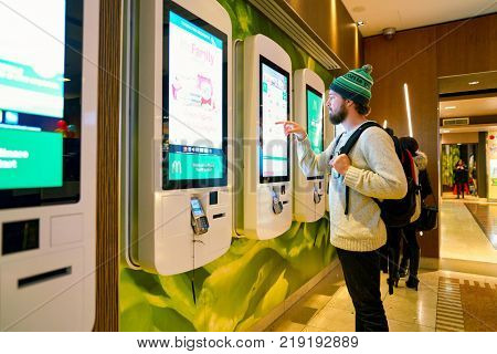 MILAN, ITALY - CIRCA NOVEMBER, 2017: customer at a McDonald's store place orders and pay through self ordering kiosk.