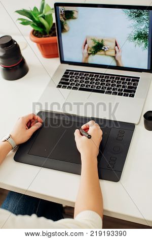 retouching on computer laptop using digital tablet and stylus pen