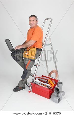 Builder typing on a laptop