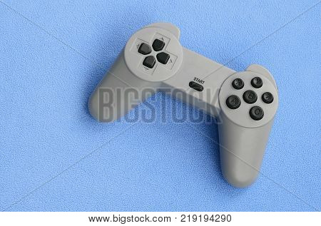 Playing games concept. Single pad joystick lies on the blanket of furry blue fleece fabric. Controller for video games on a background texture of light blue soft plush fleece material poster