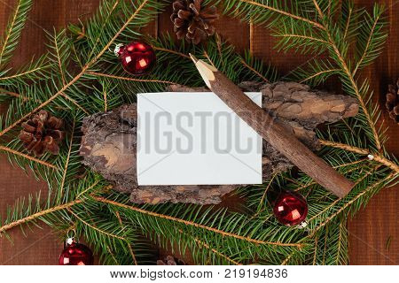 Christmas or New Year wish list with fir tree branches, bark, Christmas balls and blank paper for wish list or New Year resolutions. Top view and copy space for text