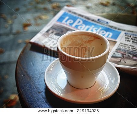 Paris France - September 9 2017: An empty coffee cup and Le Parisien newspaper on the cafe table.