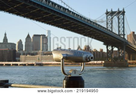 Coin-operated binoculars against a Manhattan Bridge - view from Brooklyn Bridge Park.