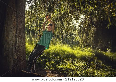 Smiling boy playing outdoors in forest  among fir trees in countryside during summer sunset symbolizing happy carefree childhood in countryside