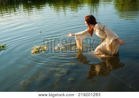Attractive red-hair woman with national dress in water of lake. Russian traditional Ivan Kupala holiday celebration