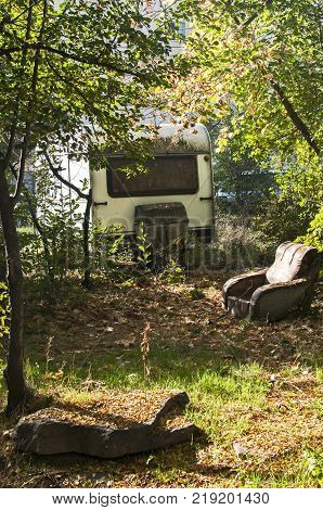 Old vintage abandoned grunge caravan and shabby armchair in overgrown with vegetation place