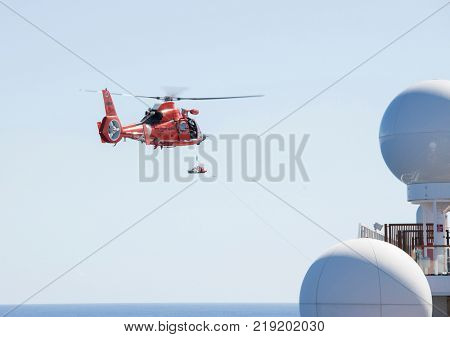 NORTH ATLANTIC OCEAN-DECEMBER 12, 2017: The United States Coast Guard engages in a medical rescue from a ship in the North Atlantic Ocean.