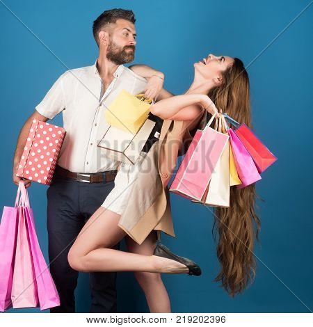 Fashion shopaholic couple. Couple in love hold shopping bag near blue wall. Shopping and sale. Girl and bearded man hold present pack cyber Monday. Black Friday happy holiday relations.