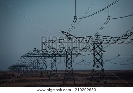 Ecology eco power technology concept. Electric energy transmission. Electricity distribution stations. Power line towers in desert on blue sky background. Global warming climate change.