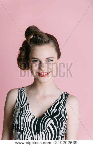pinup youth and look. Makeup hairdresser and cosmetics. Woman with retro hair and fashionable makeup pinup. Girl in stylish vintage dress on pink background. Beauty and fashion cosmetics.