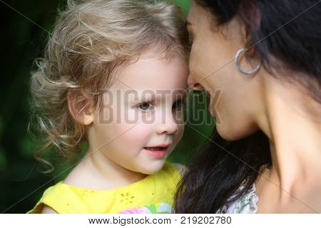 Happy mother smile with daughter outdoor. Woman hold girl kid on summer day. Family parenting love trust. Mothers day concept. Child care childhood.